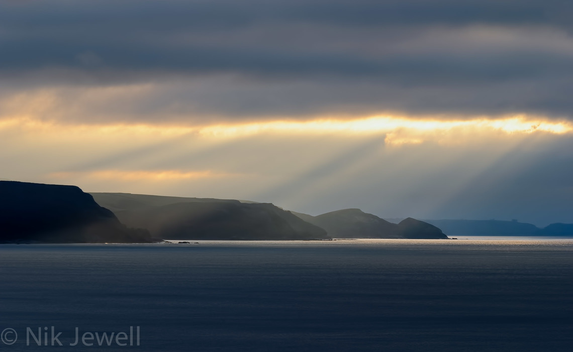 Image of crepuscular rays illuminating the coast near Crackington Haven