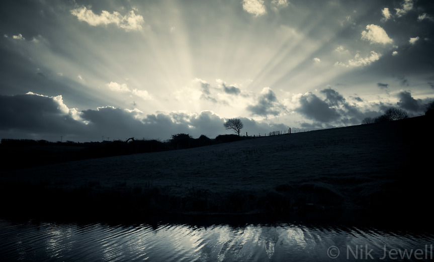 Godbeams (crepuscular rays) appearing as the sun sets behind the ridge that separates the canal from the sea at Bude Canal in North Cornwall.