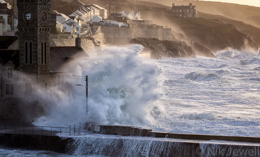 Image of wave crashing against clock tower at Porthleven