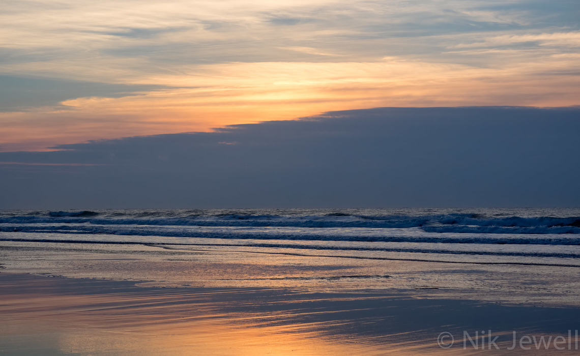 Post sunset pastel shades in the sky and reflected on the beach at Sandymouth near Bude in North Cornwall.