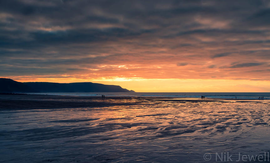 The sun about to drop below a layer of dark clouds during sunset at Widemouth Bay, North Cornwall.