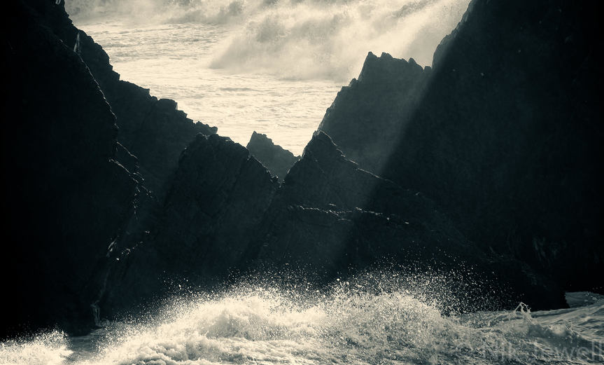 Beams of light illuminating a wave-lashed gap in the teeth-like rocks south of Hartland Quay during the fourth atlantic storm of 2014