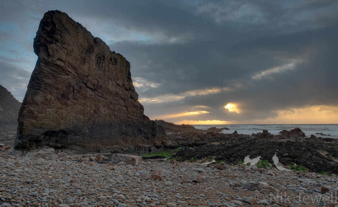 Godbeams (crepuscular rays) behind the fin of Unshore Rock at Northcott Mouth near Bude in North Cornwall