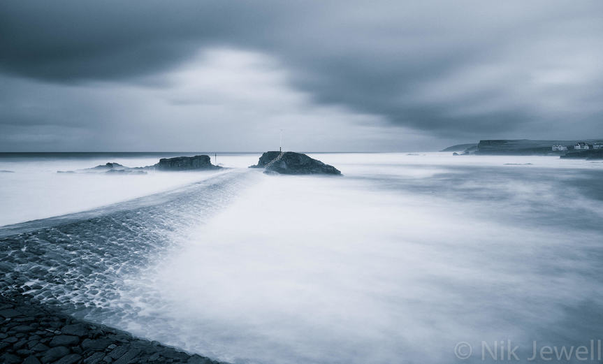 A moody and atmospheric shot of the first January storm surge overtopping the breakwater at Bude in North Cornwall