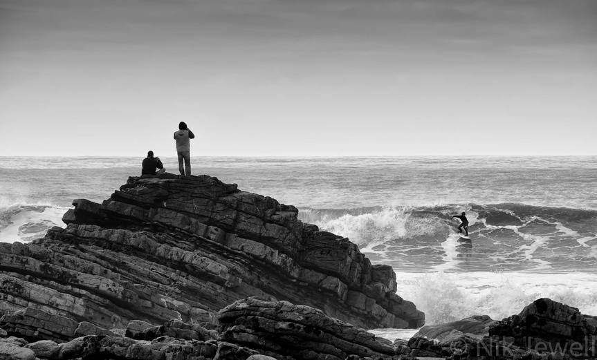 Two men surf watching a surfer on a wave at Millook Haven near Bude in North Cornwall