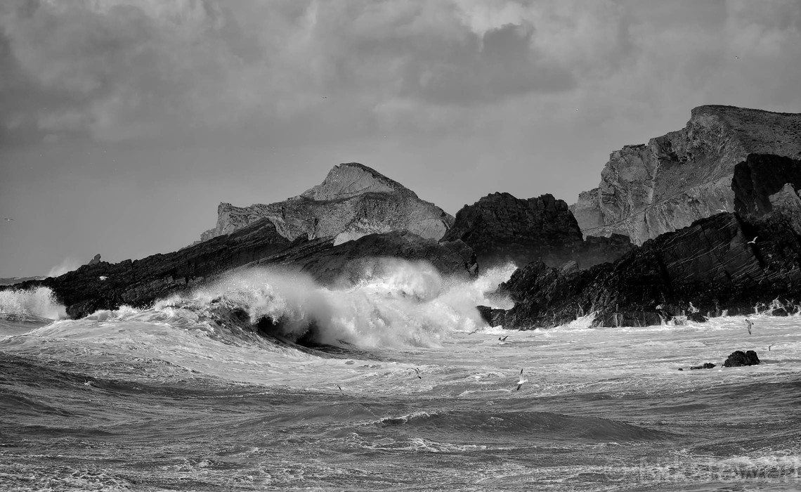 A big wave breaking with gulls flying in front of it with the rocks to the North of Hartland Quay, North Devon behind