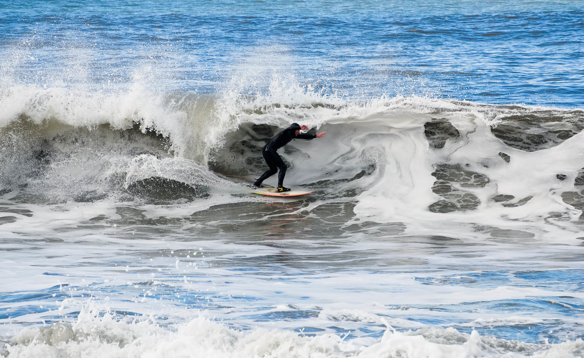 A surfer on a white water wave at Millook Haven near Bude in North Cornwall