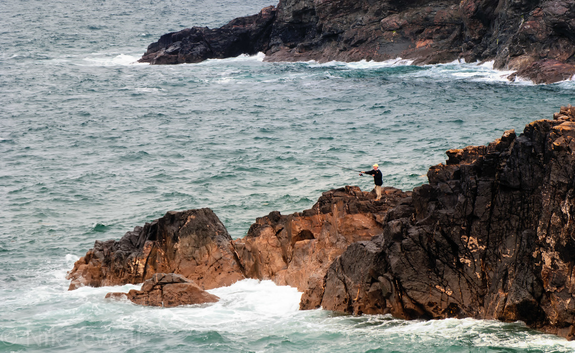 Image of fisherman casting on the rocks at Lundy Bay