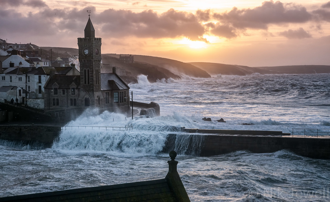 Image of waves overflowing harbour wall at dawn at Porthleven