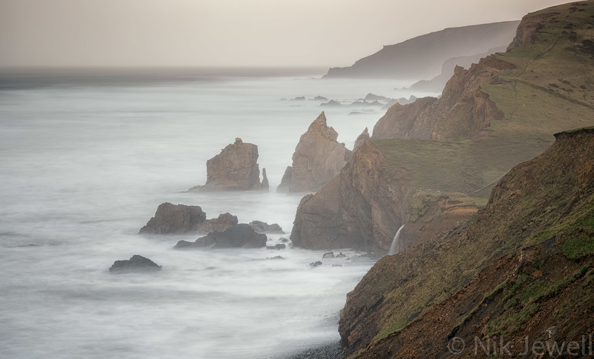 Long exposure image of the waves hitting the beach at Sandymouth