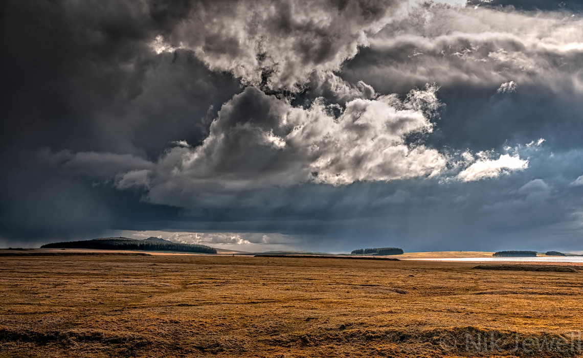 Stunning light illuminates Rough Tor and Crowdy Reservoir across Davidstow Airfield on Bodmin Moor near Camelford in North Cornwall.