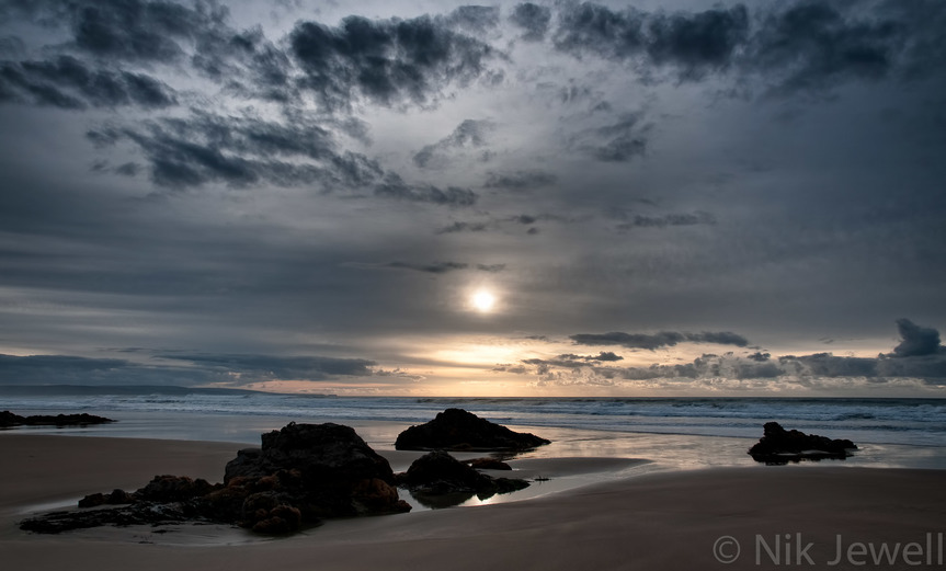 Late afternoon shot of a misty sun through dark clouds over the sea and foreground rocks on the beach at Menachurch Point near Bude in North Cornwall