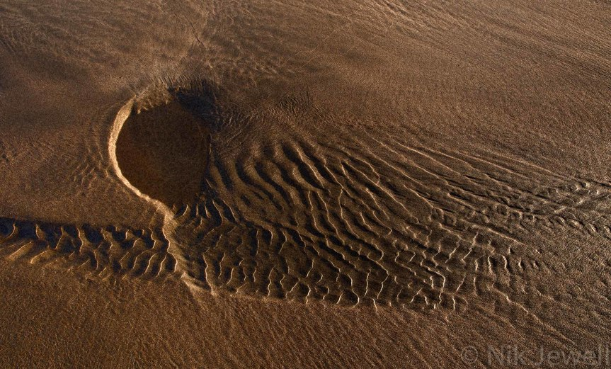 Natural sand sculpture left by the tide at Sandymouth near Bude in North Cornwall resembling an angel in flight