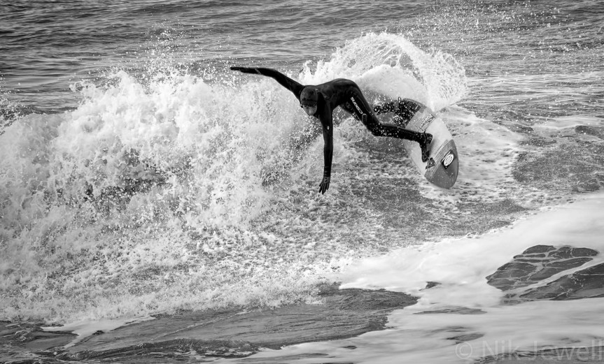 Surfer executing a top turn at Millook