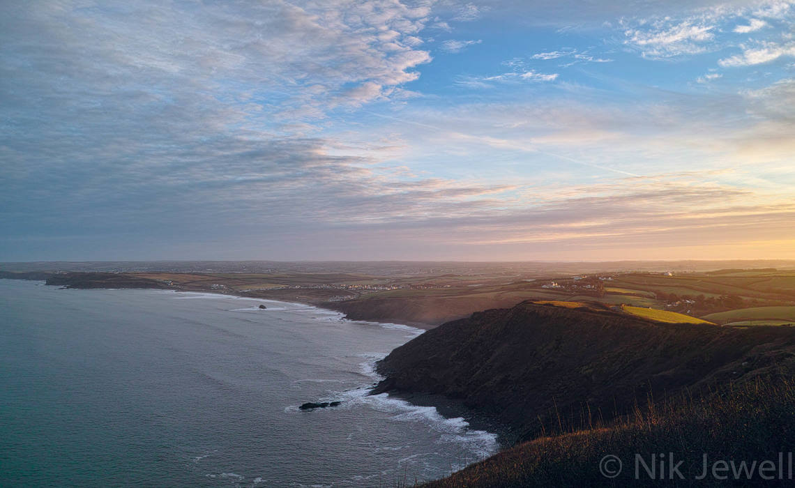 The view from Penhalt Cliff at Dawn of Widemouth Bay, nearby coastline, a mackerel sky and a distant temperature inversion